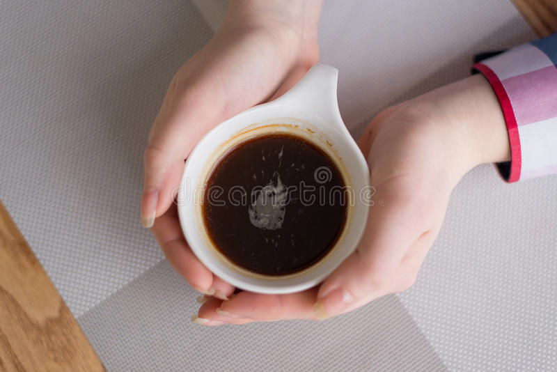 Hands hugging a Cup of coffee on the table royalty free stock photo