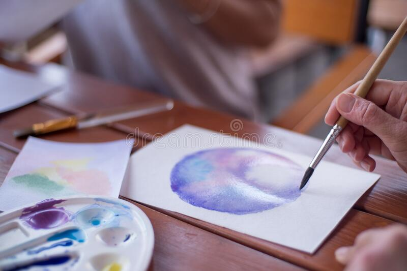 Hands of human closeup draws with watercolor brush royalty free stock images