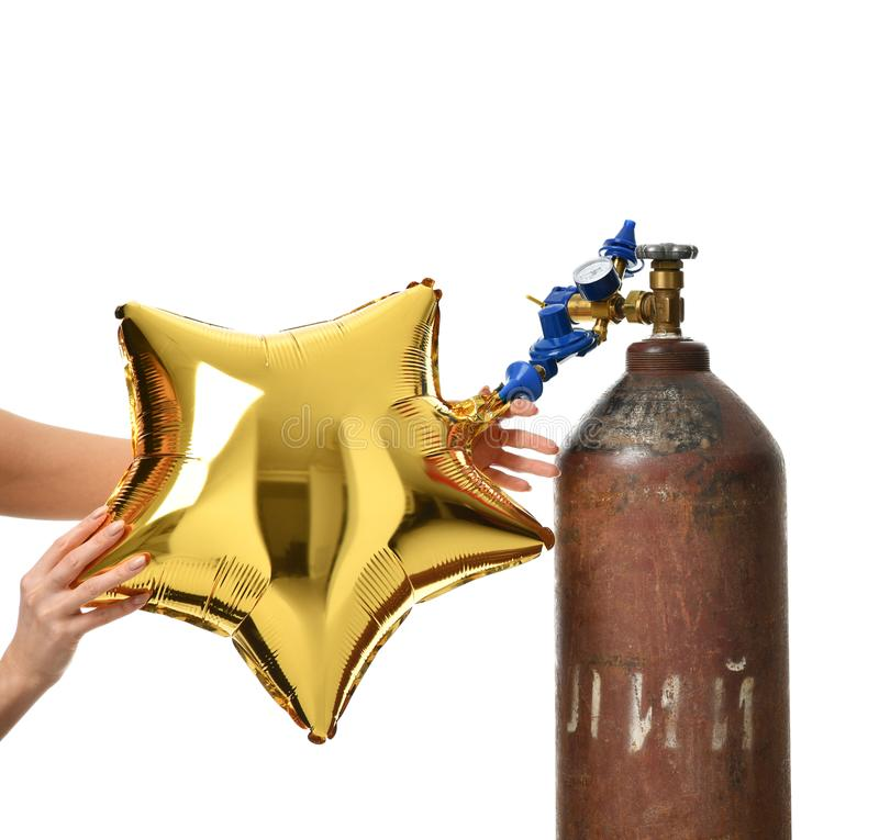 Hands inflate gold star balloon use Helium Tank with Economy Regulator Fill Valve. For Latex Balloons isolated on white background stock photo
