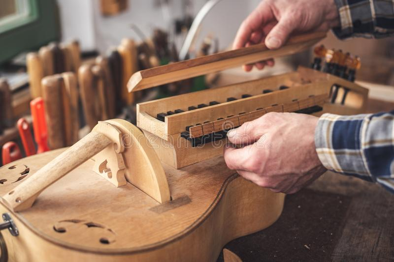 Hands of an instrument maker working on a Hurdy Gurdy stock photography