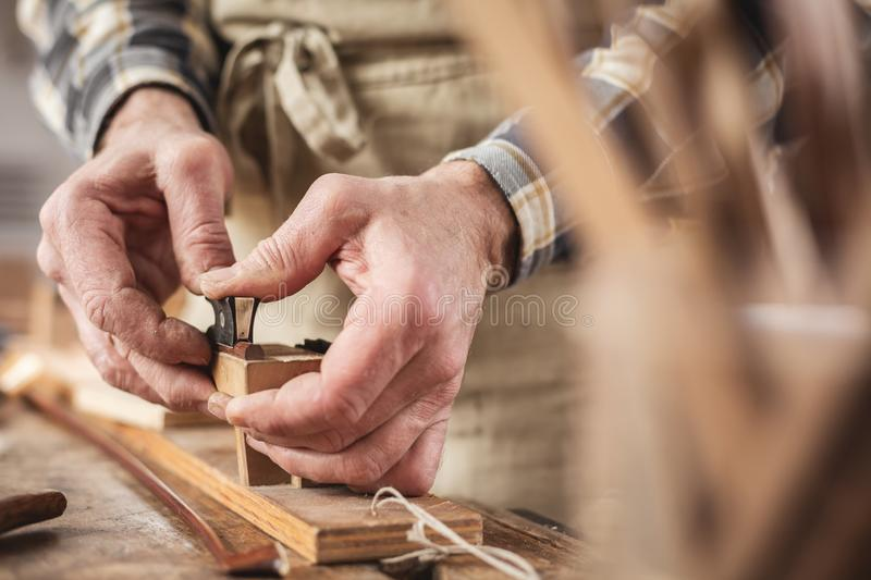Hands of an instrument maker working on a violin bow. Detail shot of the hands of a mature craftsperson. The hands are attaching the frog on a violin bow stock photos