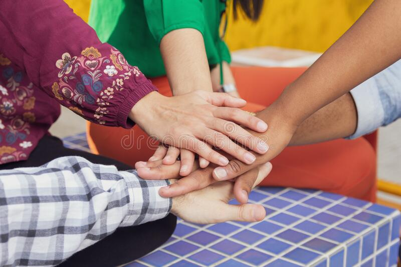 Hands joined. All together in a team. Teamwork and unity. Men and women come together to cooperate and work. Hands joined, one over the other. All together in a royalty free stock photography