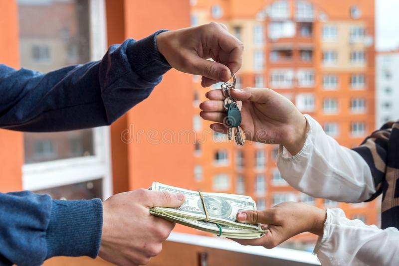 Hands with keys from new apartment and dollar bunch.  stock images