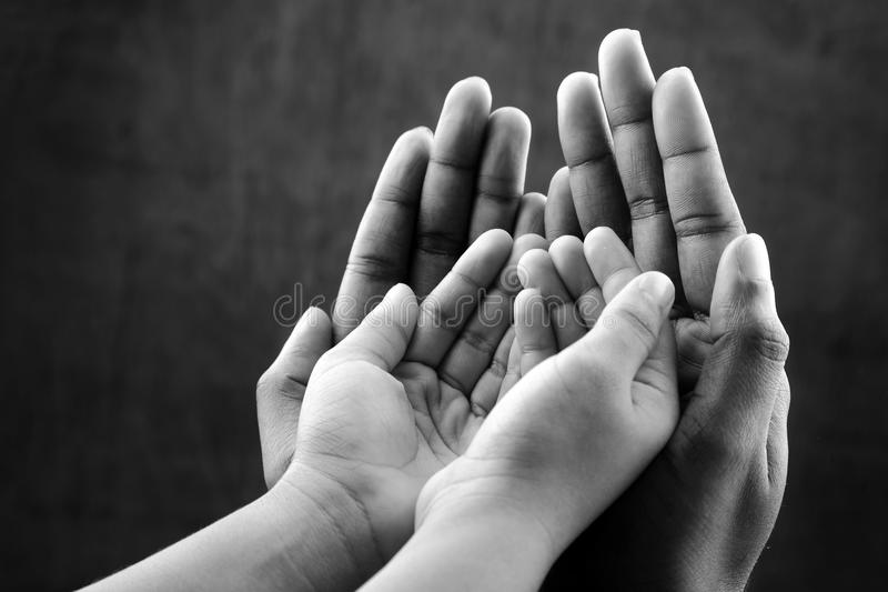 Hands of a kid covered by hands of as elder. stock image