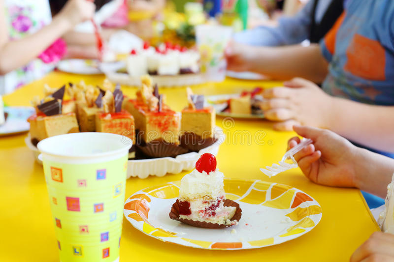 Hands of kids eating delicious little cakes on yellow table. Focus on cake royalty free stock photo
