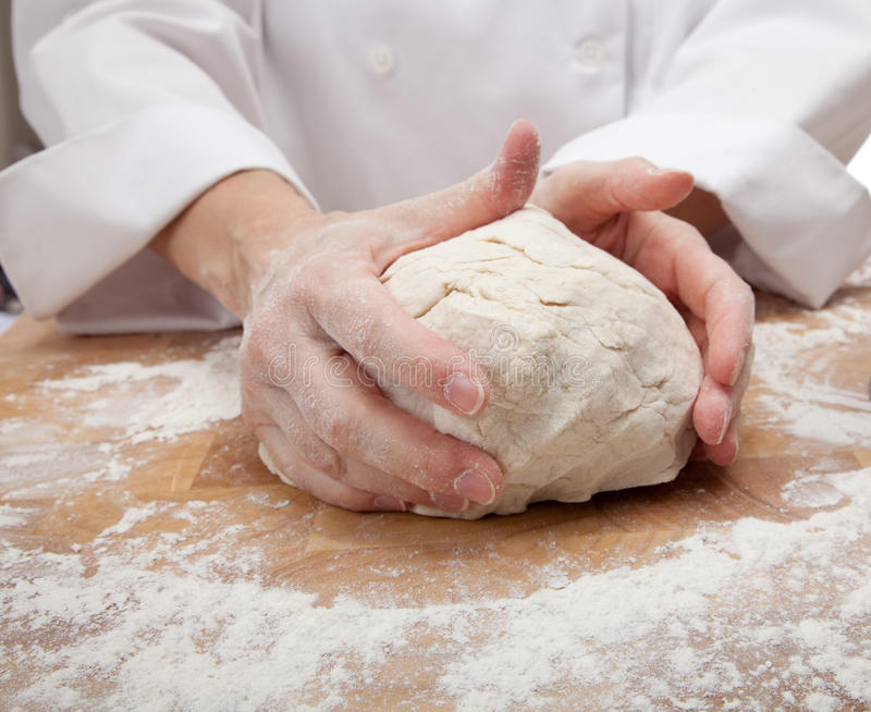Hands kneading bread dough. On a cutting board royalty free stock photo