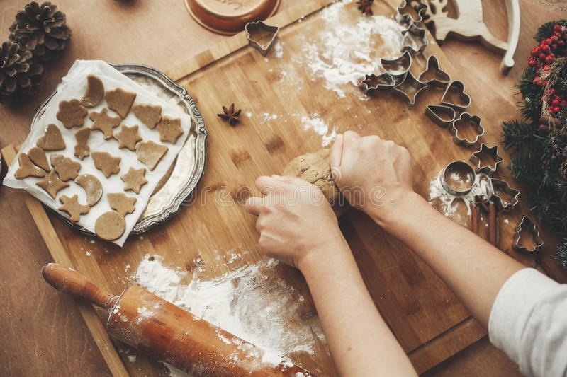 Hands kneading dough for gingerbread cookies on rustic table on stock photography