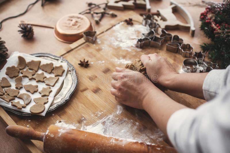 Hands kneading dough for gingerbread cookies on rustic table on. Background of wooden rolling pin, cookies, metal cutters, christmas decorations. Atmospheric royalty free stock images