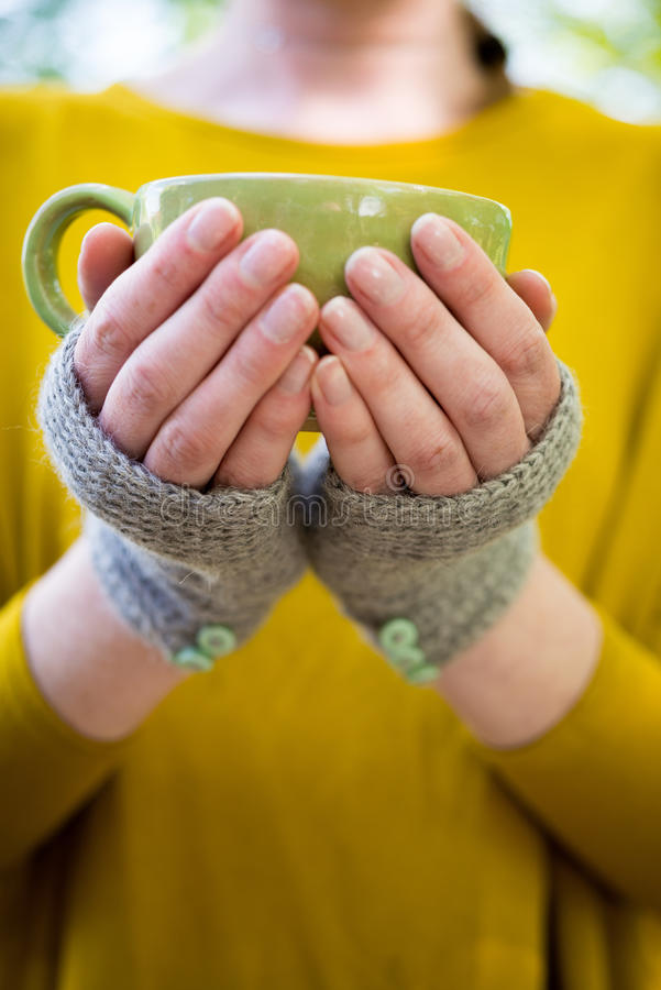 Hands in Knitted Fingerless Gloves Holding a Cup royalty free stock photography
