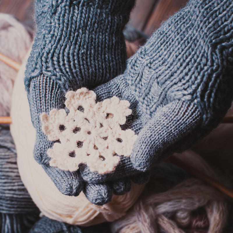 Hands in knitted gloves. Hands in a grey gloves holding white knitted snowflake as a winter symbol royalty free stock image