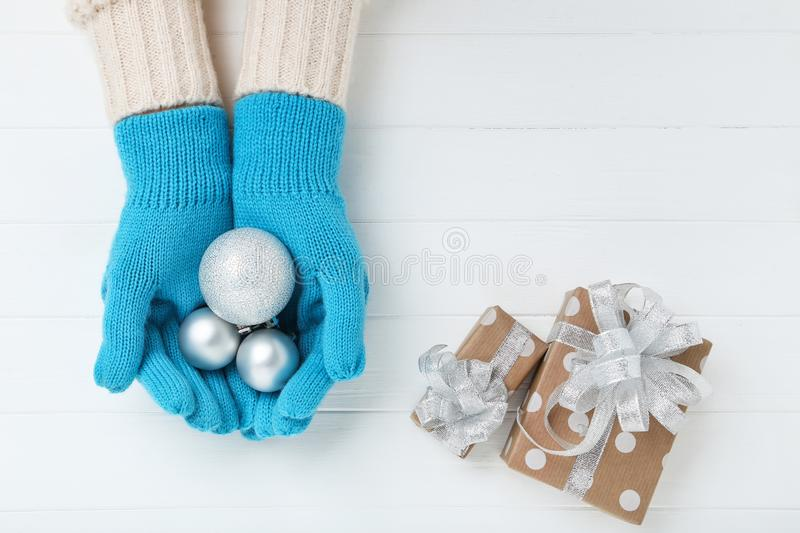Hands in mittens holding baubles stock image