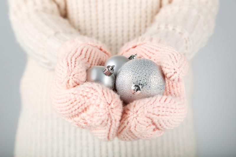 Hands in mittens holding christmas baubles royalty free stock image