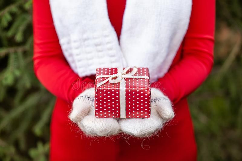 Hands in knitted mittens holding Christmas giftbox, Concept of Xmas surprise. Girl hands in white knitted mittens holding a small handmade red Christmas giftbox royalty free stock images