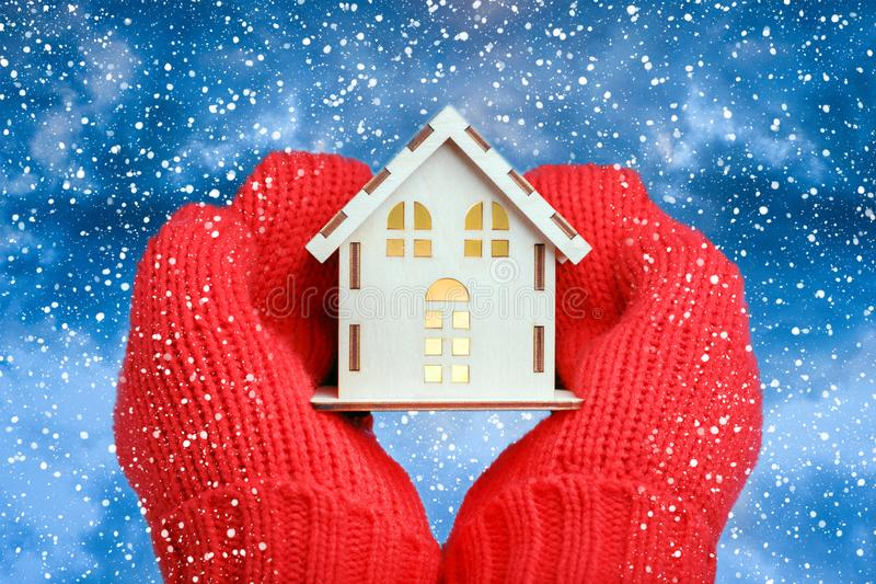 Hands in knitted mittens Holding model House on snowfall background. House Energy Efficiency Concept. royalty free stock photography
