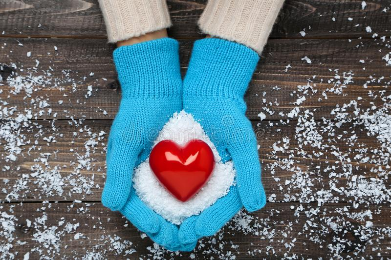Hands in mittens holding red heart stock images