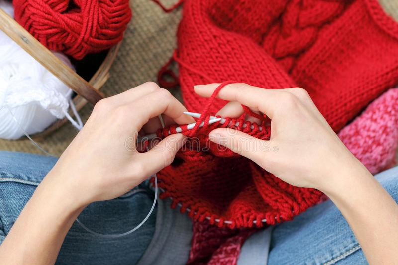 Warming hobbies home. Hands knitting with red yarn, garments for the winter season stock photo