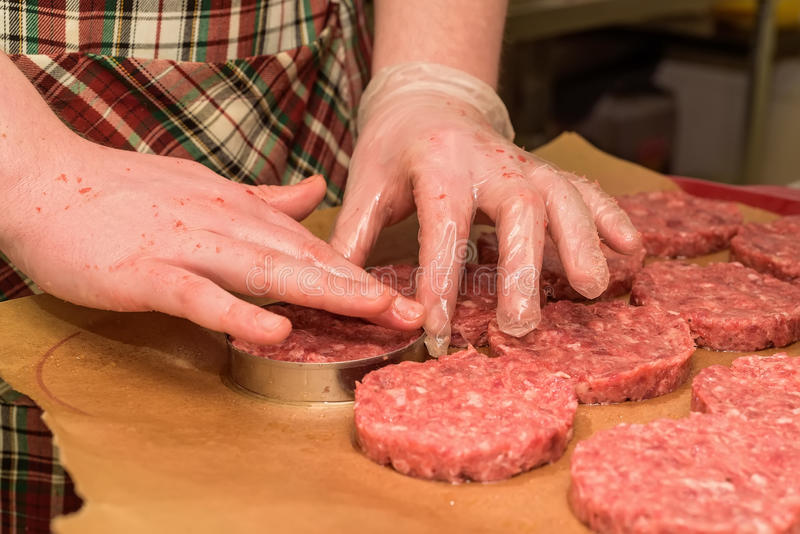 Hands kooking burger cutlets close up. Hands in plastic gloves touch raw round cutlets made of ground beef royalty free stock photography