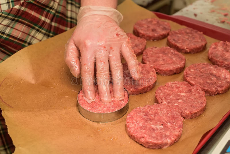 Hands kooking burger cutlets close up. Hands in plastic gloves touch raw round cutlets made of ground beef stock image