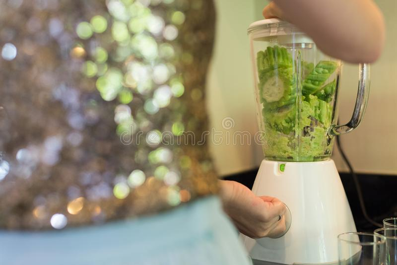 hand of lady with pieces of fresh green gourd in electric blender in kitchen. stock image