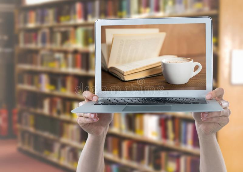 Hands with laptop showing book and coffee against blurry bookshelf. Digital composite of Hands with laptop showing book and coffee against blurry bookshelf stock photos