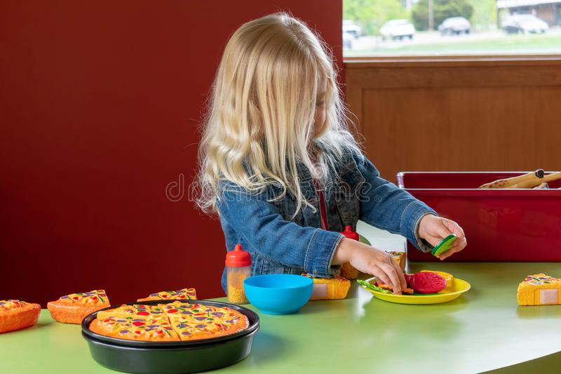 Little girl playing with pretend food stock photos