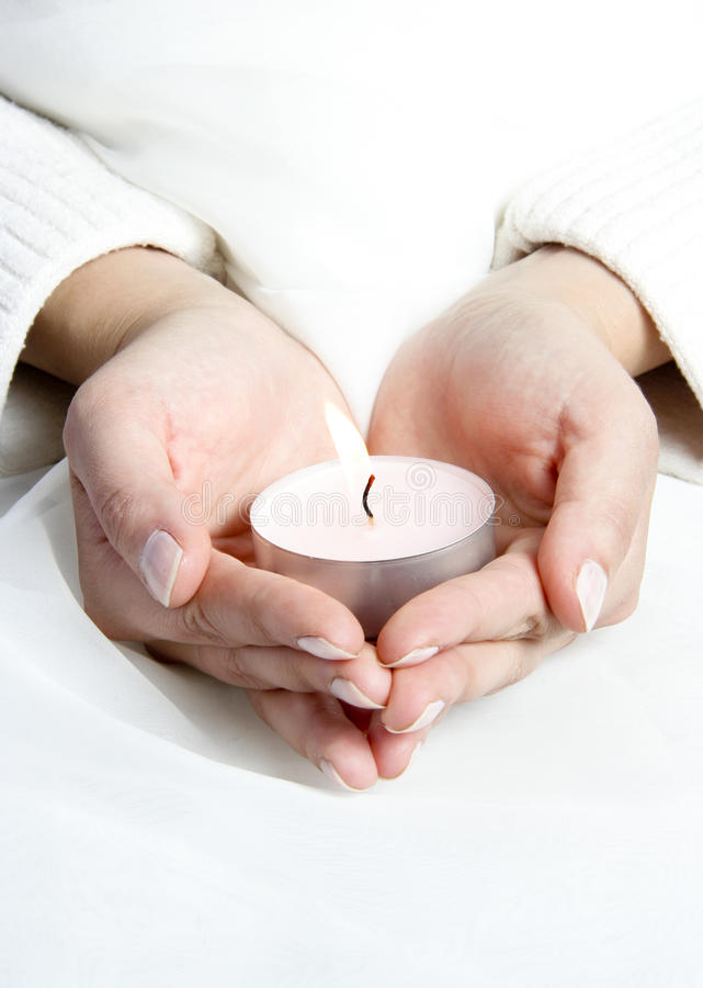Hands with lighted candle. Female with white clothes holding lighted candle in hands stock image