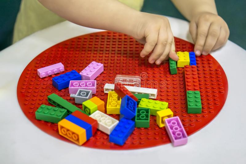 Hands of little child playing with constructor from bricks royalty free stock images