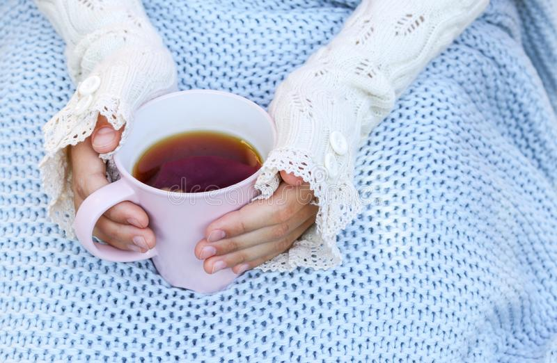 Hands of little girl in cozy hand warmers fingerless gloves holding cup of tea on her knees wrapped in warm knitted plaid. Hugge or lagom style. Cold season royalty free stock image