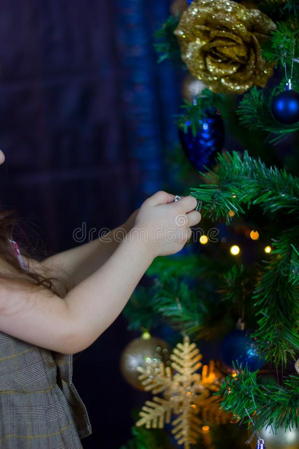 Hands of little girl decorating christmas tree by blue balls. stock images