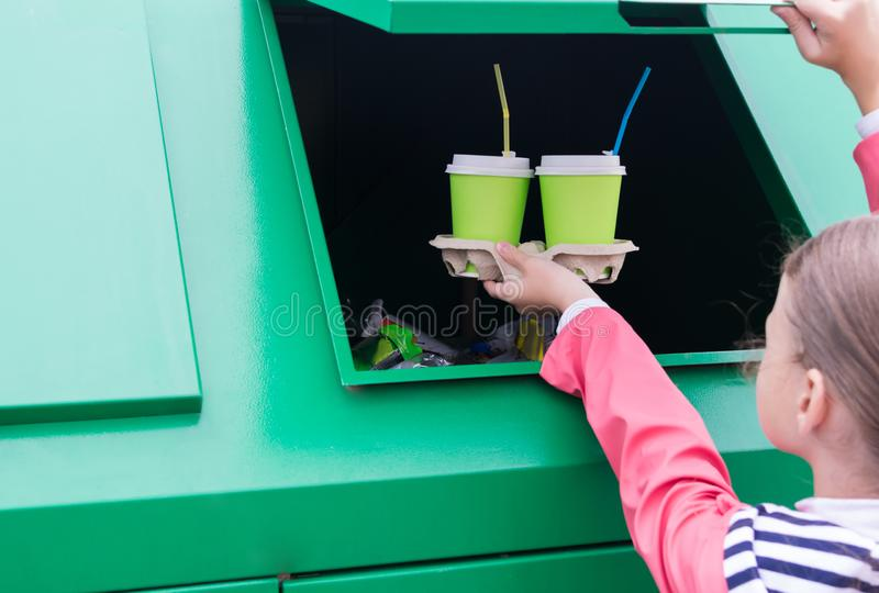 Hands of a little girl hold three paper cups in front of a trash tank royalty free stock photography