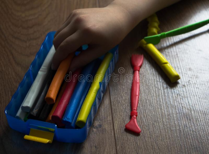 The hands of the little girl take out the multi-colored clay royalty free stock photo
