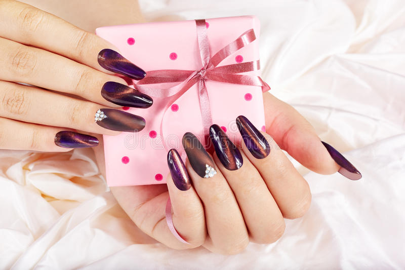 Hands with long artificial manicured nails holding a gift box. Hands with long purple artificial manicured nails holding a gift box with bow stock photo