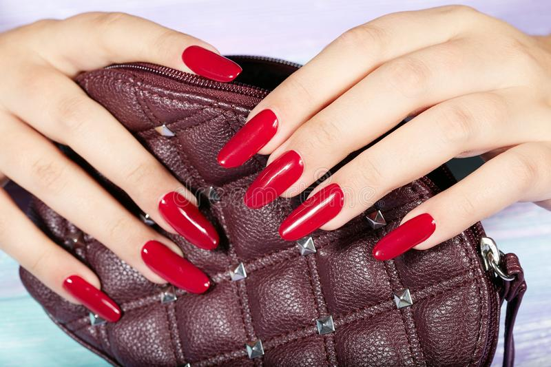 Hands with long artificial manicured nails holding a handbag. Hands with long artificial manicured nails colored with red nail polish holding a handbag royalty free stock photography