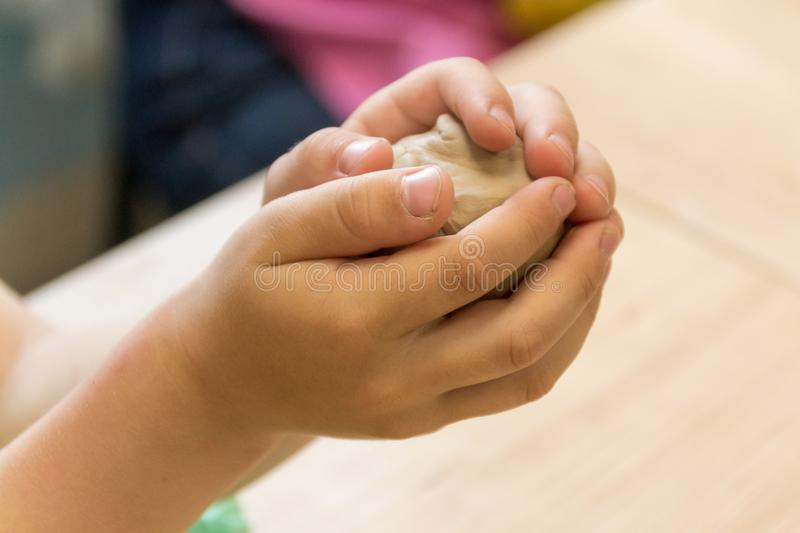 Hands make crafts from clay. Creativity. Transformation of clay into crafts. stock photography