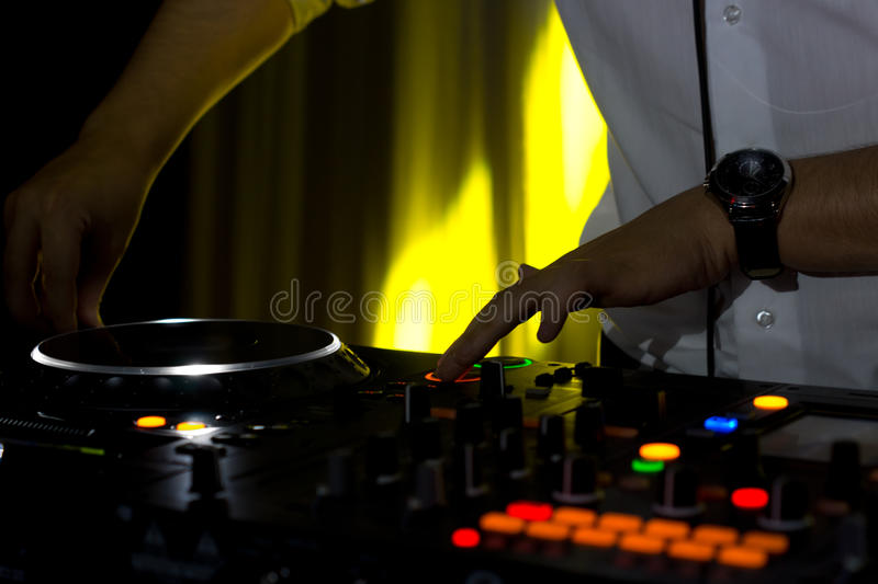Hands of a male disc jockey mixing music. On his deck and turntables at night with colourful lighting on the switches and controls stock images
