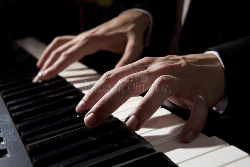 hands male leka för piano arkivbild