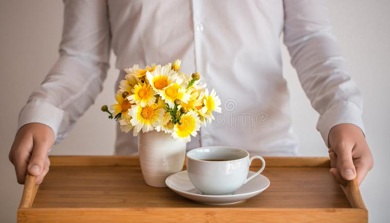 The hands of a man in a white shirt are holding a tray with a cup of coffee / tea and a bouquet of daisies against his chest royalty free stock photo