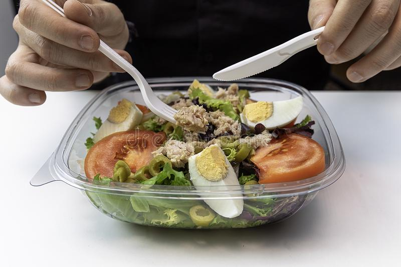 Hands of a man with a delicious salad of tuna, egg and vegetables royalty free stock images