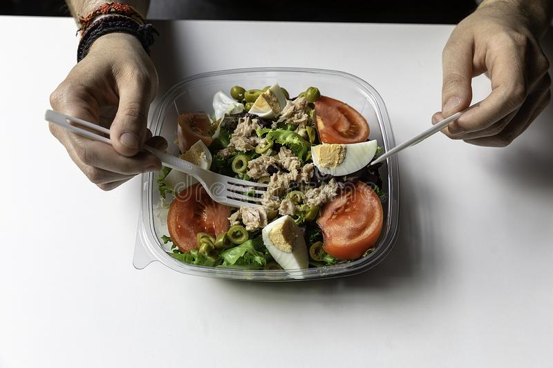 Hands of a man with a delicious salad of tuna, egg and vegetables royalty free stock image