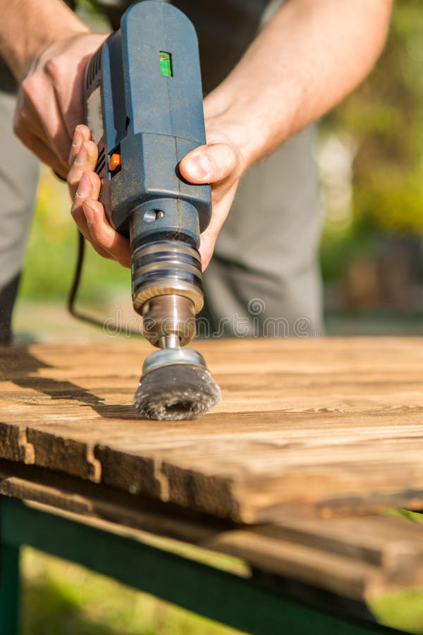 Hands man with electrical rotating brush metal disk sanding a piece of wood. Woodworking outdoors royalty free stock images