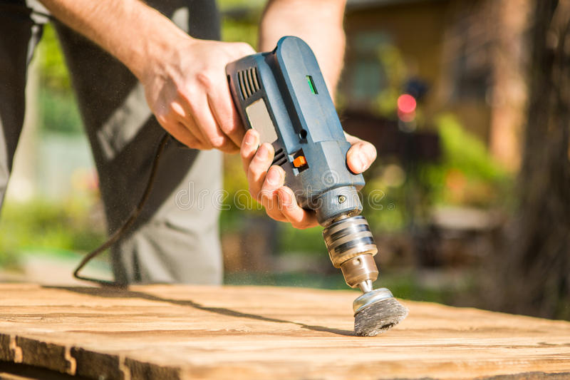 Hands man with electrical rotating brush metal disk sanding a piece of wood. Woodworking outdoors stock image