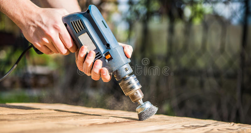 Hands man with electrical rotating brush metal disk sanding a piece of wood. Woodworking outdoors royalty free stock image