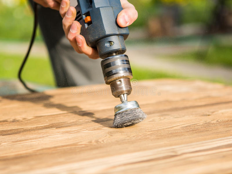 Hands man with electrical rotating brush metal disk sanding a piece of wood. Woodworking outdoors stock photos