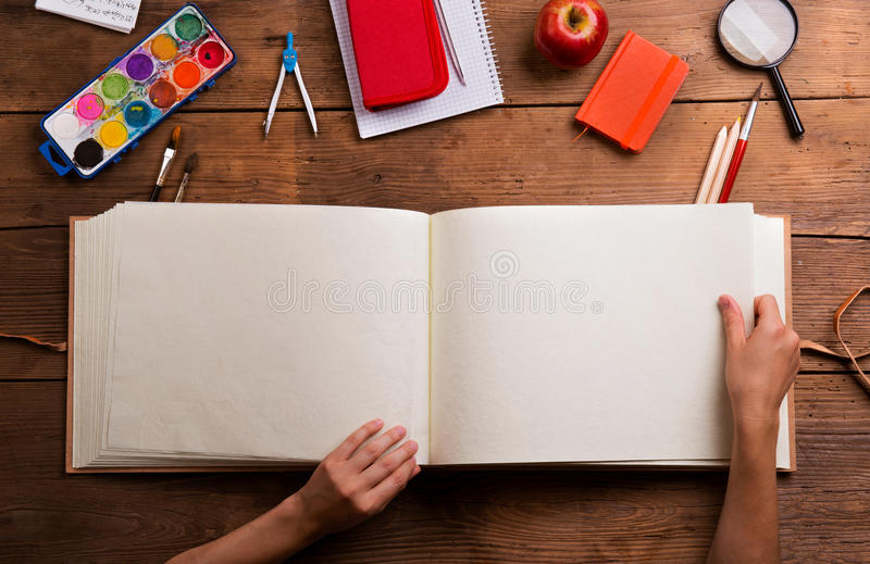 Hands of man with empty notebook. Various school supplies. Hands of man with empty notebook. Various school supplies, flat lay, copy space. Studio shot on stock image