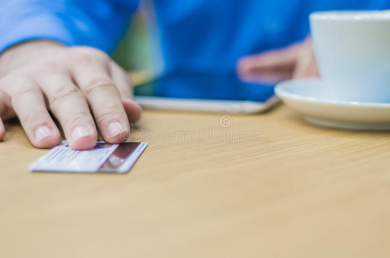 Hands of man giving plastic card to waiter to pay for the order. Business man paying with a credit or debit card royalty free stock photo