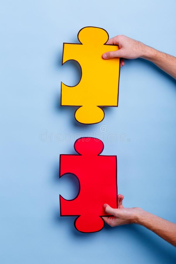 The hands of the man hold two red and yellow puzzles. Blue background. Close-up. royalty free stock images