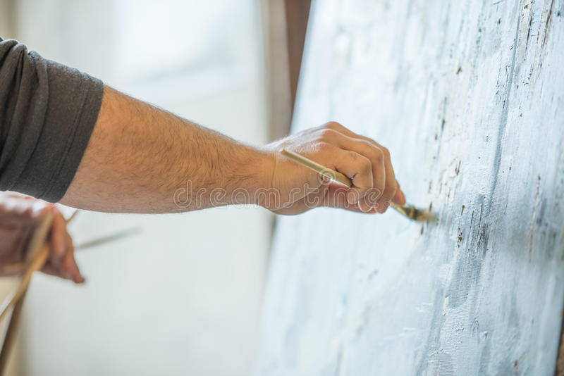 Hands of a man holding a brush and painting on a canvas royalty free stock photography
