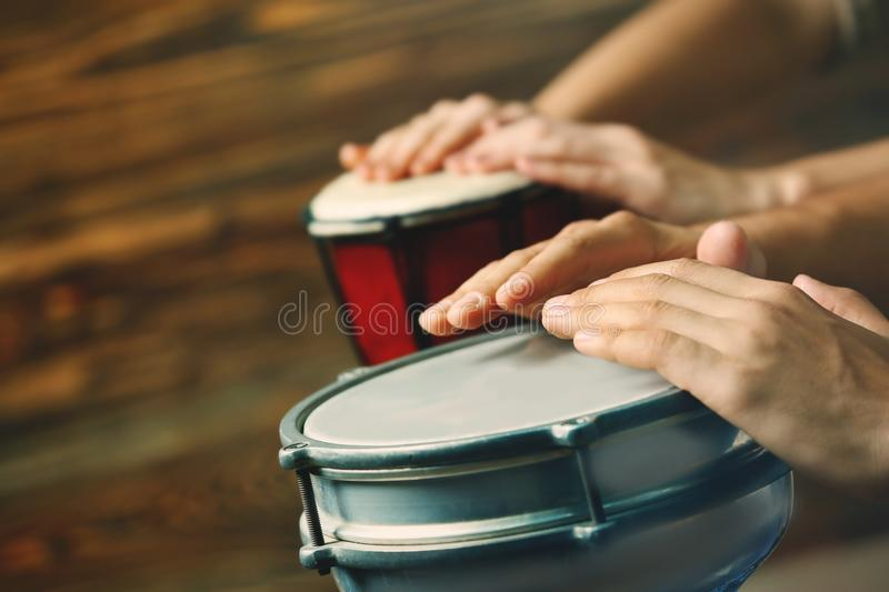 Hands of man playing African drum on brown background stock photos