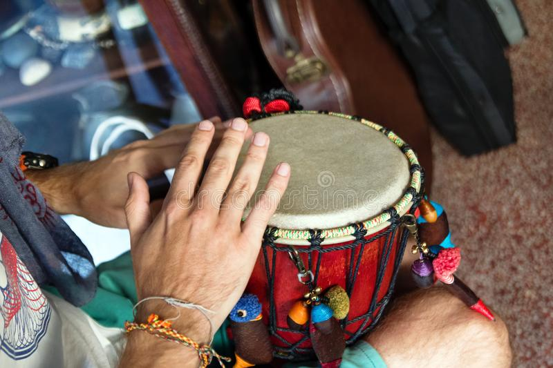 Hands of man playing African drum or djembe inside a music shop. royalty free stock images