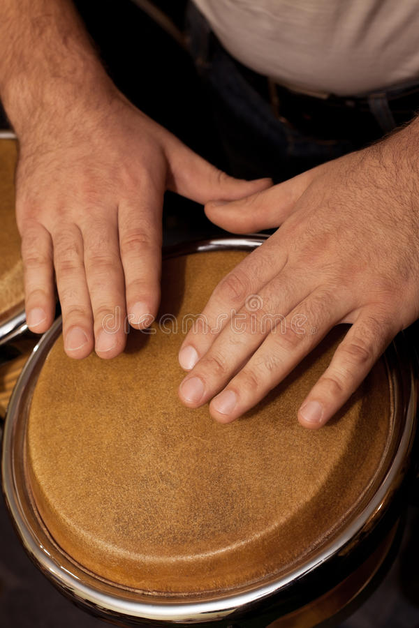 Hands of man playing the bongos royalty free stock photo